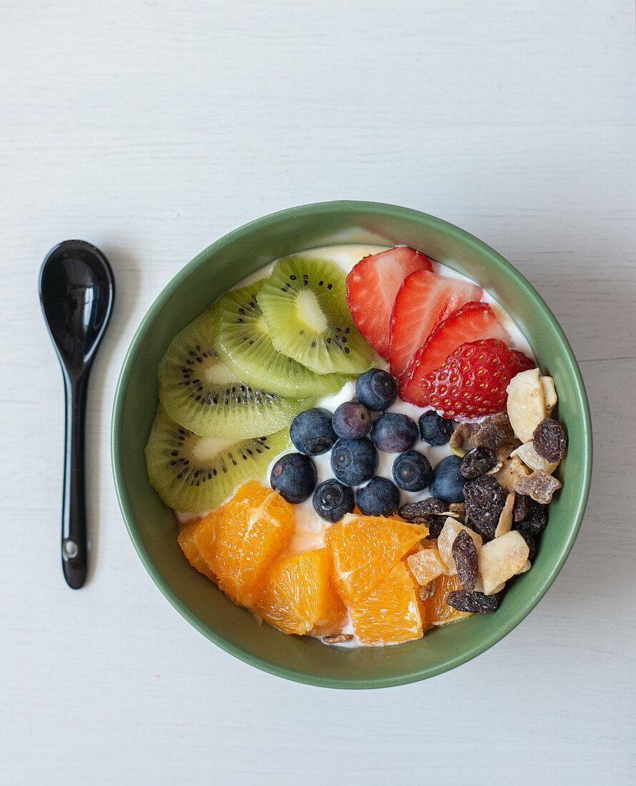Breakfast Bowl mit Kiwi, Orangen, Blaubeeren, Erdbeeren und Trockenfrüchten