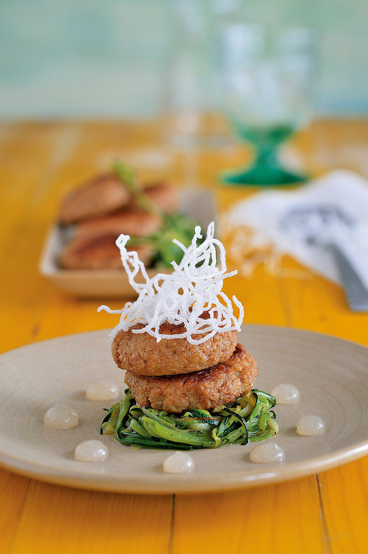 Vegan millet and fig cakes on courgette noodles with lime drops