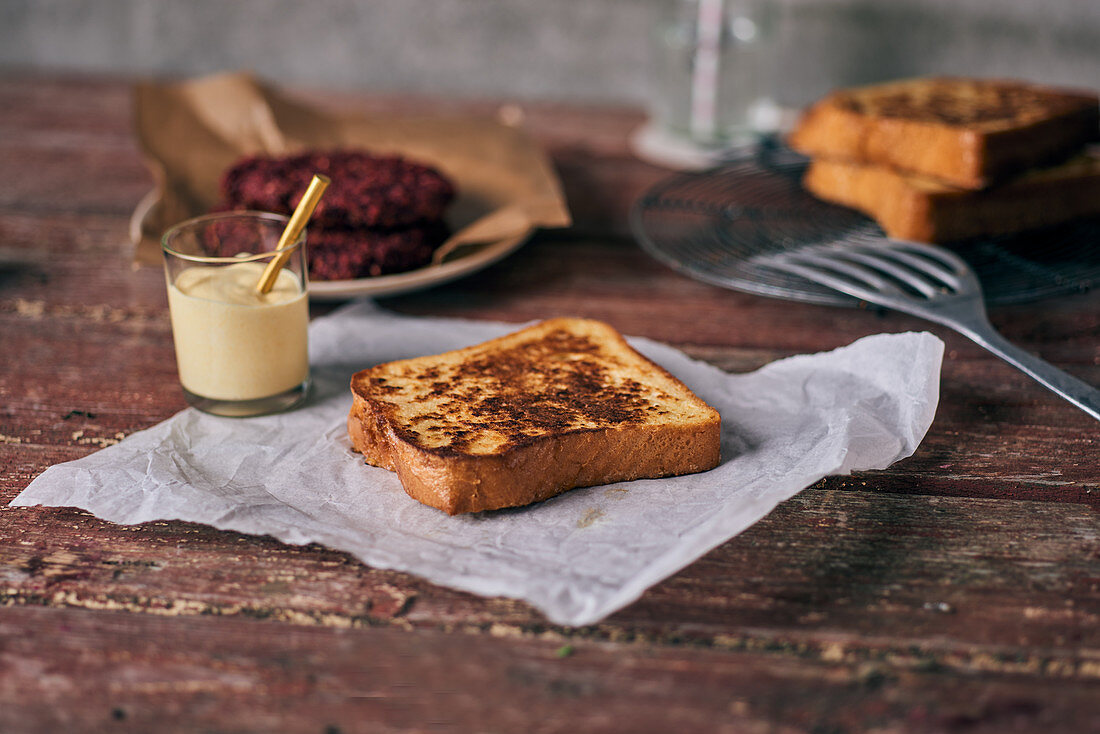 French toast on paper with mayonnaise and a beetroot burger