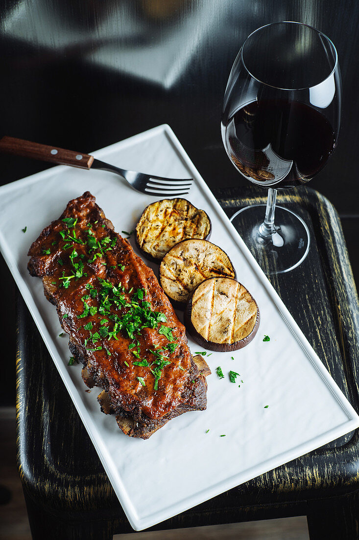 Grilled pork ribs garnished with fresh parsley served with sliced grilled eggplant on white tray