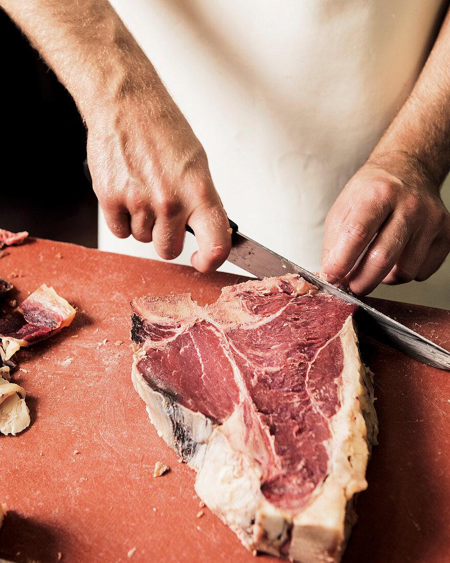 Cutting a dry aged T-bone steak