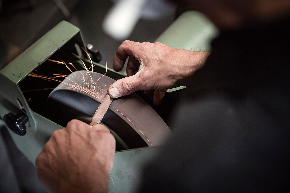 A knife being sharpened on a buffing machine