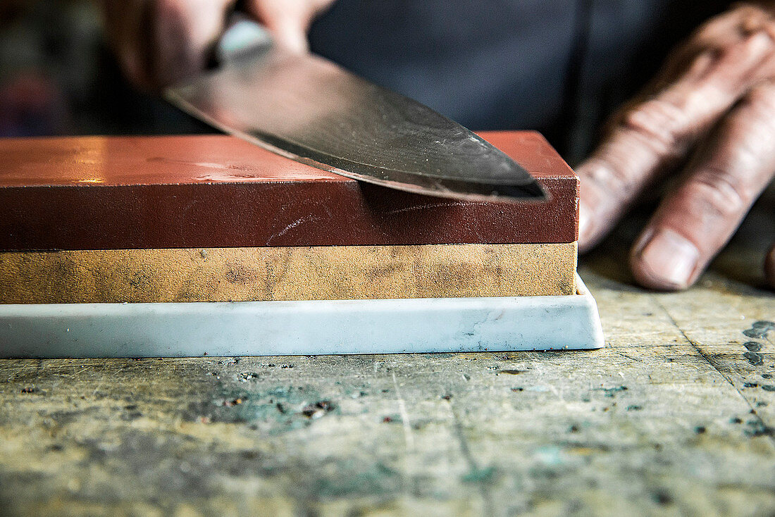 A knife being sharpened on a whetstone