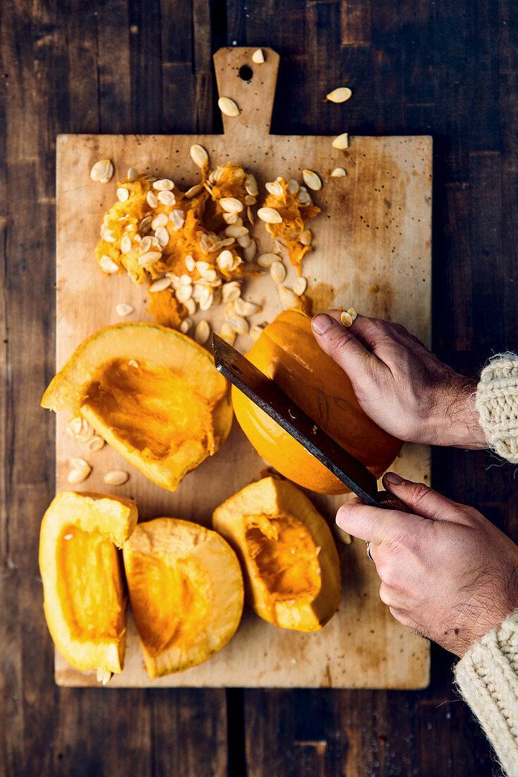 Hands cut pumpkin on wooden board