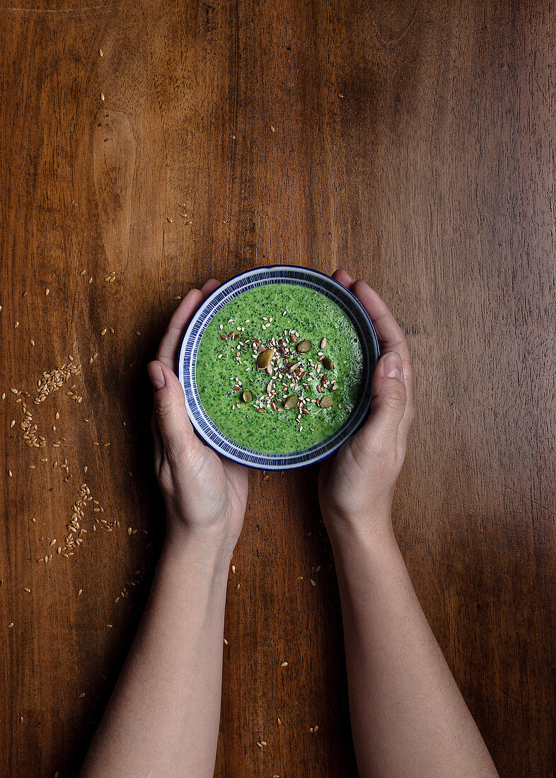 Hands holding ceramic small bowl of fresh green smoothie