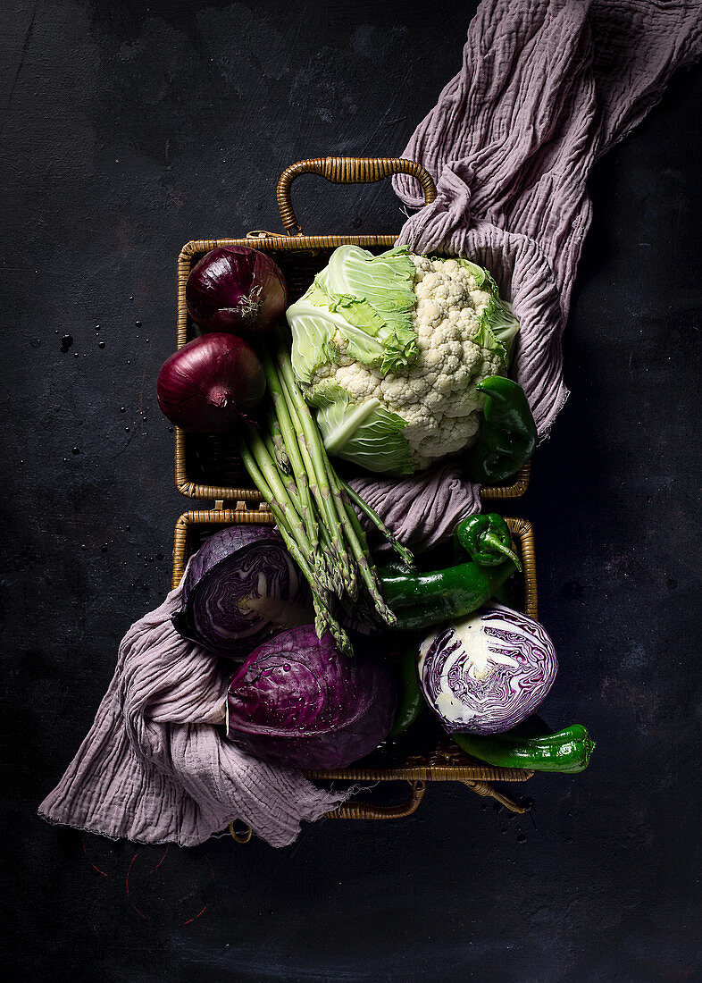Fresh ripe vegetables with violet towel in wicker basket