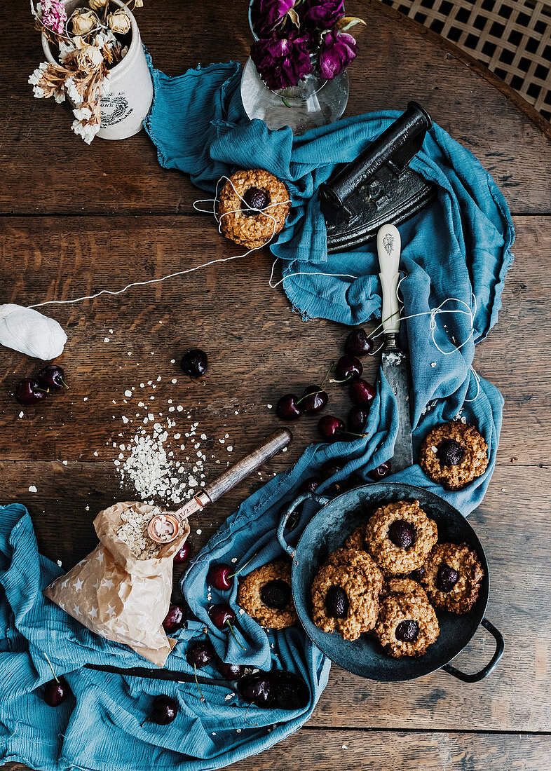 Baked cherry cookies placed on wooden table with piece of cloth and vintage iron