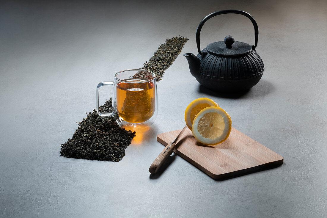 Grüner Tee in Glastasse mit Zitronen und getrockneten Teeblättern
