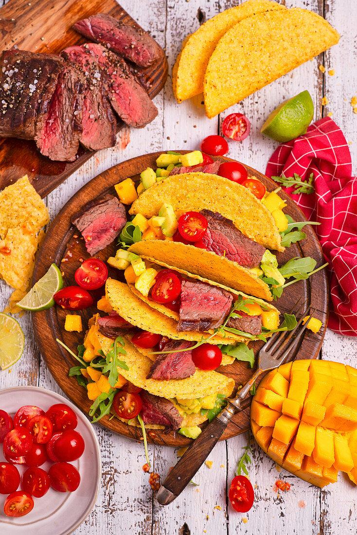 Tacos with beef, avocado, mango, arugula and tomatoes