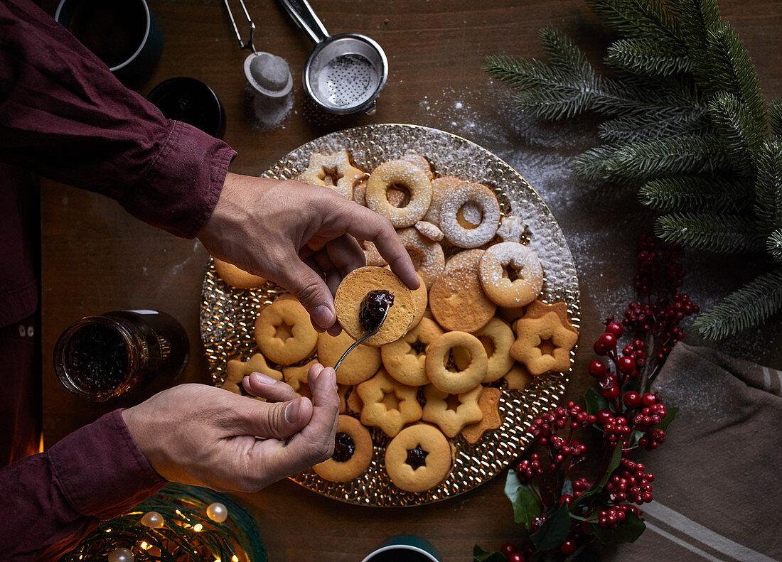 Spreading jam on freshly baked Linzer cookies