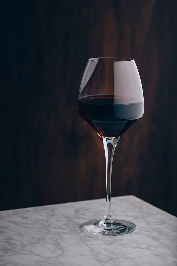 Crystal classic glass of red wine placed on marble table on black background