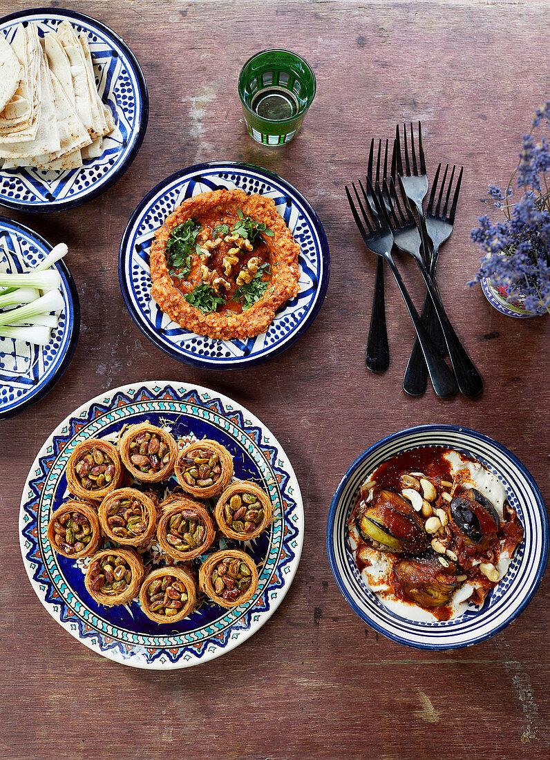 Fatteh makdous (mit Lamm gefüllte Aubergine), Muhammara (Paprikadip), Pistazien-Vogelnester  (Syrien)