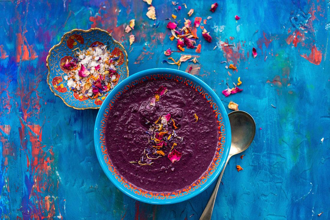Geröstete lila Karotten-Linsen-Suppe mit Meersalz und essbaren Blütenblättern