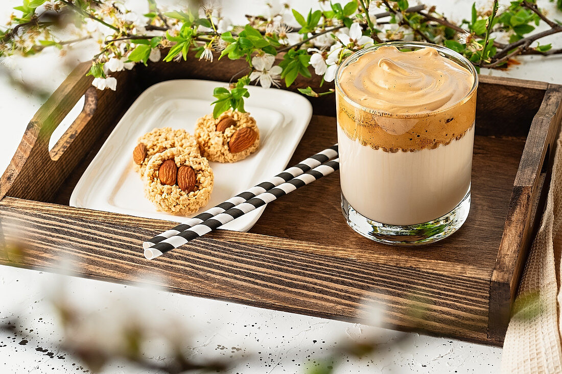 Dalgona coffee with cookies on a wooden tray