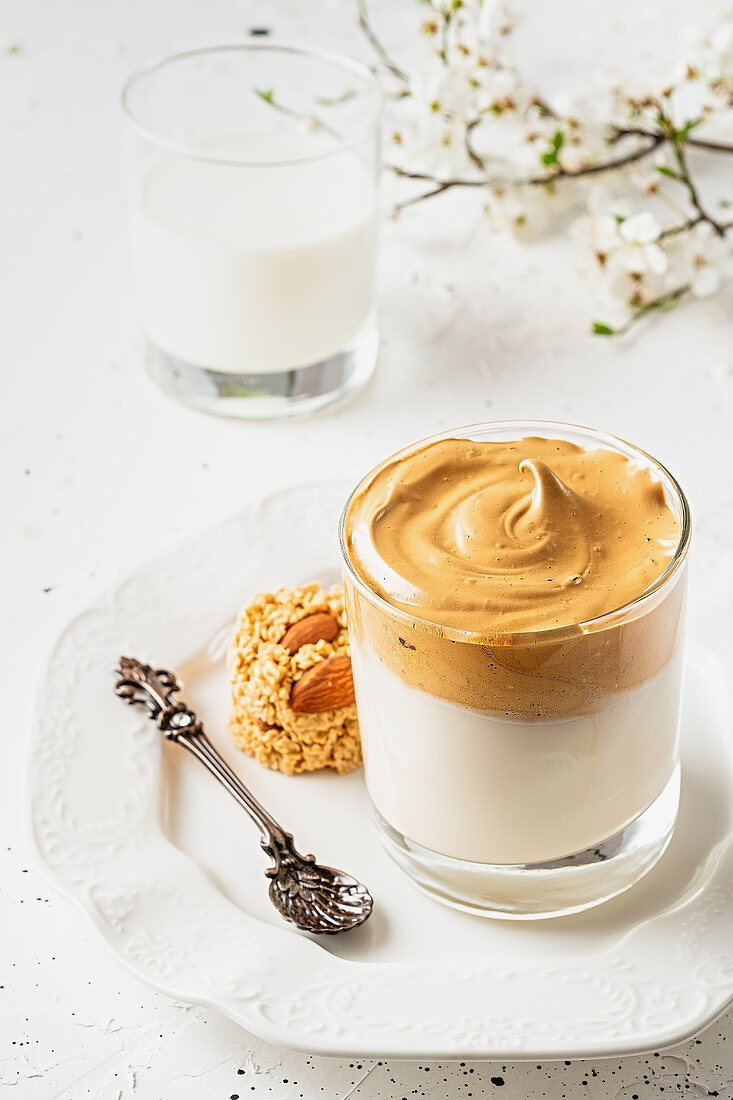 Dalgona coffee in a transparent glass with a spoon and cookies on a white plate with a bunch of blooming apple tree