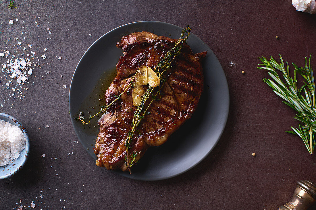 Cooked ribeye black angus prime beef steak with butter, sea salt, herbs and garlic slices