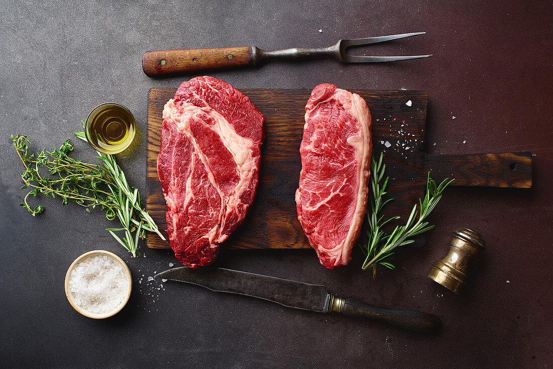 Raw black angus prime beef steaks on wooden cutting board