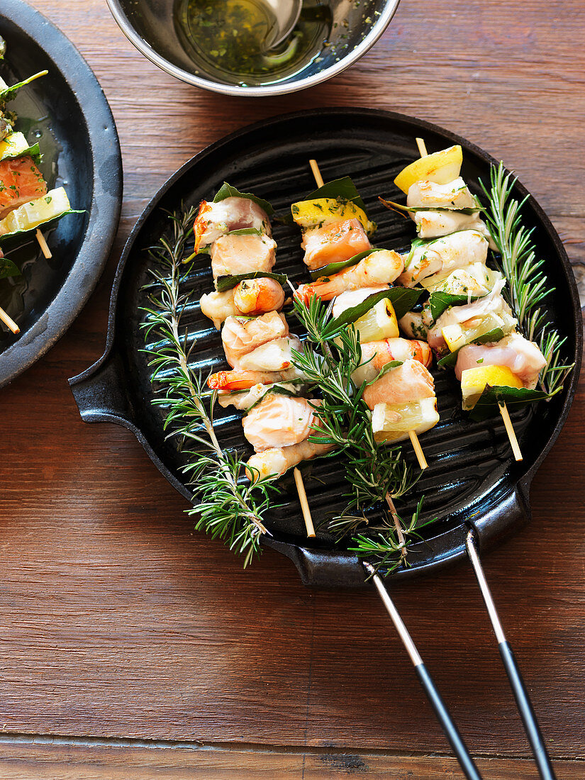 Fish skewers with rosemary in a grill pan