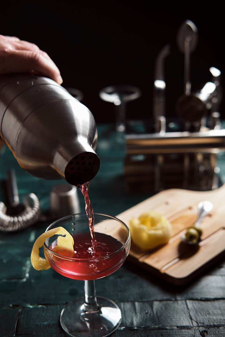 Barman pouring red alcohol cocktail from metal shaker into coupe glass garnished with lemon peel