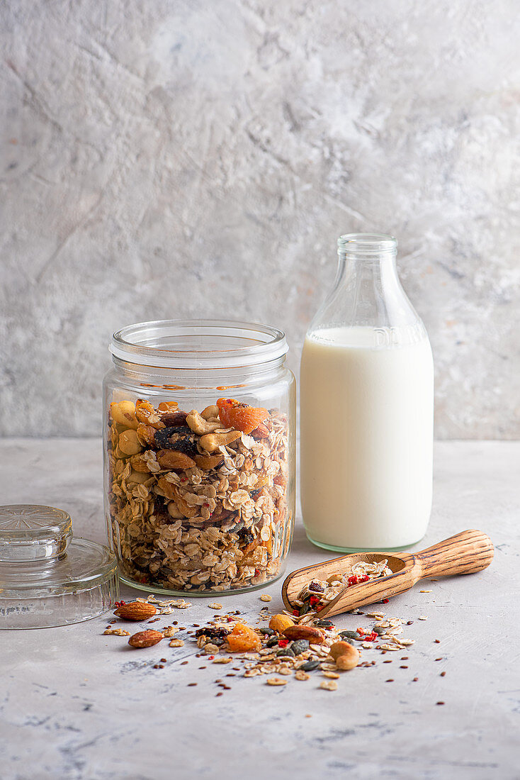 Homemade nut, seeds and fruit muesli in a jar with milk