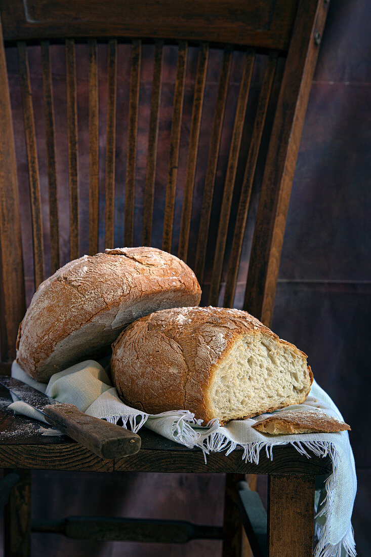 Loafs of tasty bread and sharp knife placed on piece of cloth on wooden chair