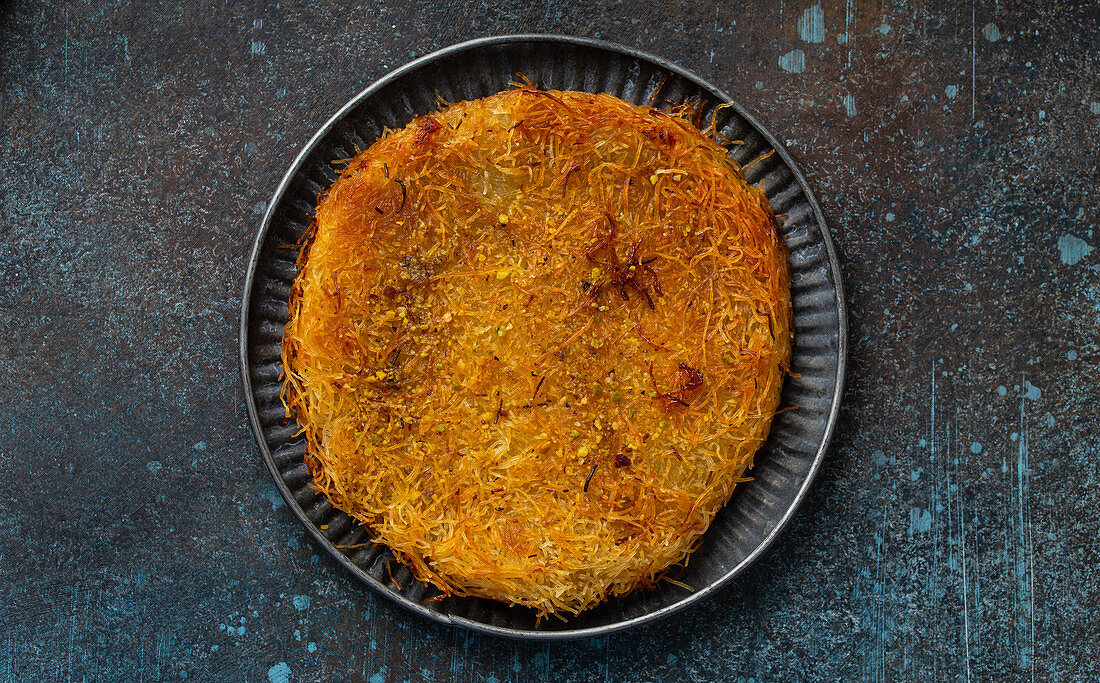 Künefe (knafeh) - traditional Turkish dessert pastry made of filo filled with cheese and syrup