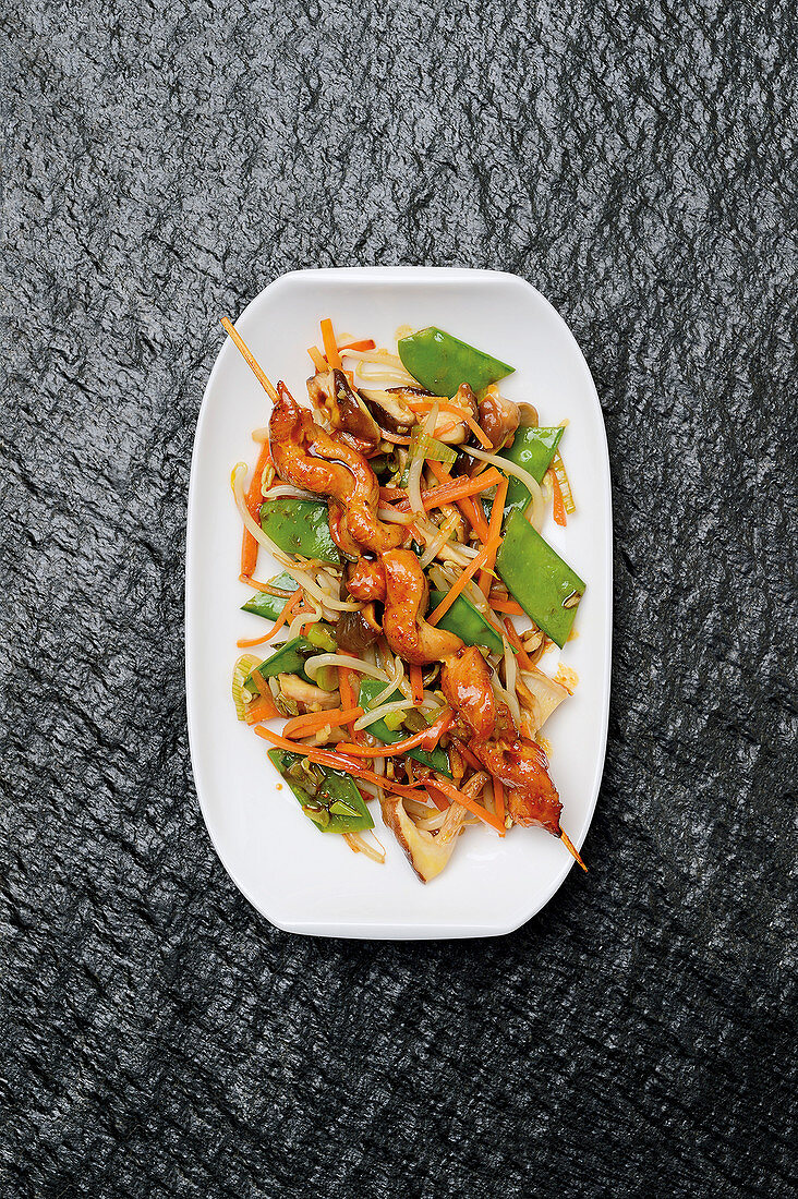 Vegetable wok with a satay skewer