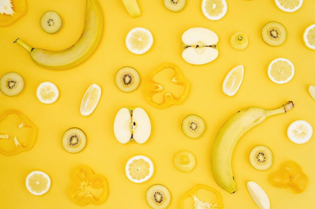Verschiedene frische Früchte und Gemüse auf gelbem Hintergrund