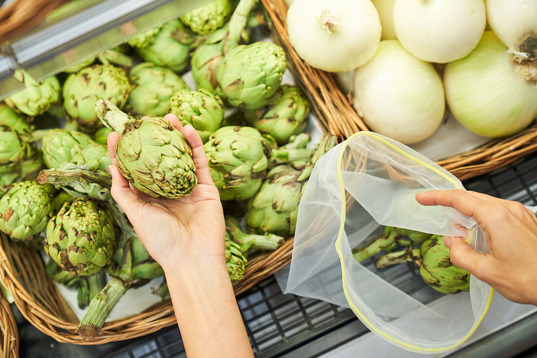 Female hand picking up artichokes from a basket with reusable bag
