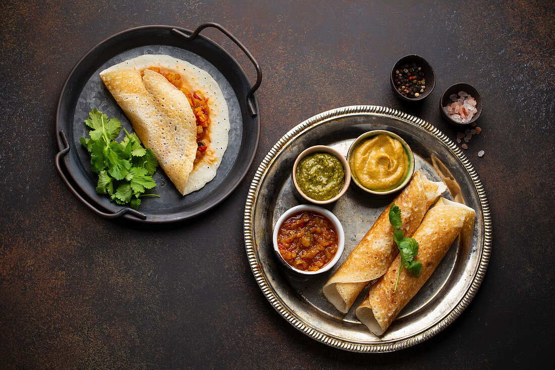 Traditional Indian rice pancakes Dosa with different dips chutney and seasonings