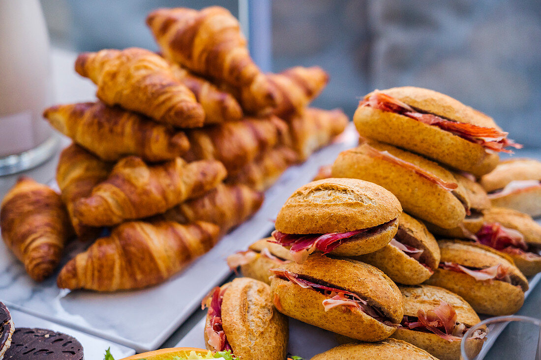 Tasty sandwiches with slices of bacon and sweet croissants served on plates for home party
