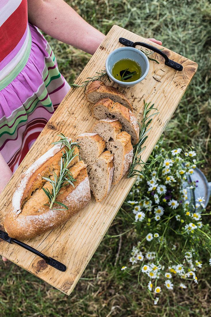 Frau hält Holzbrett mit Brot, Rosmarin und Olivenöl