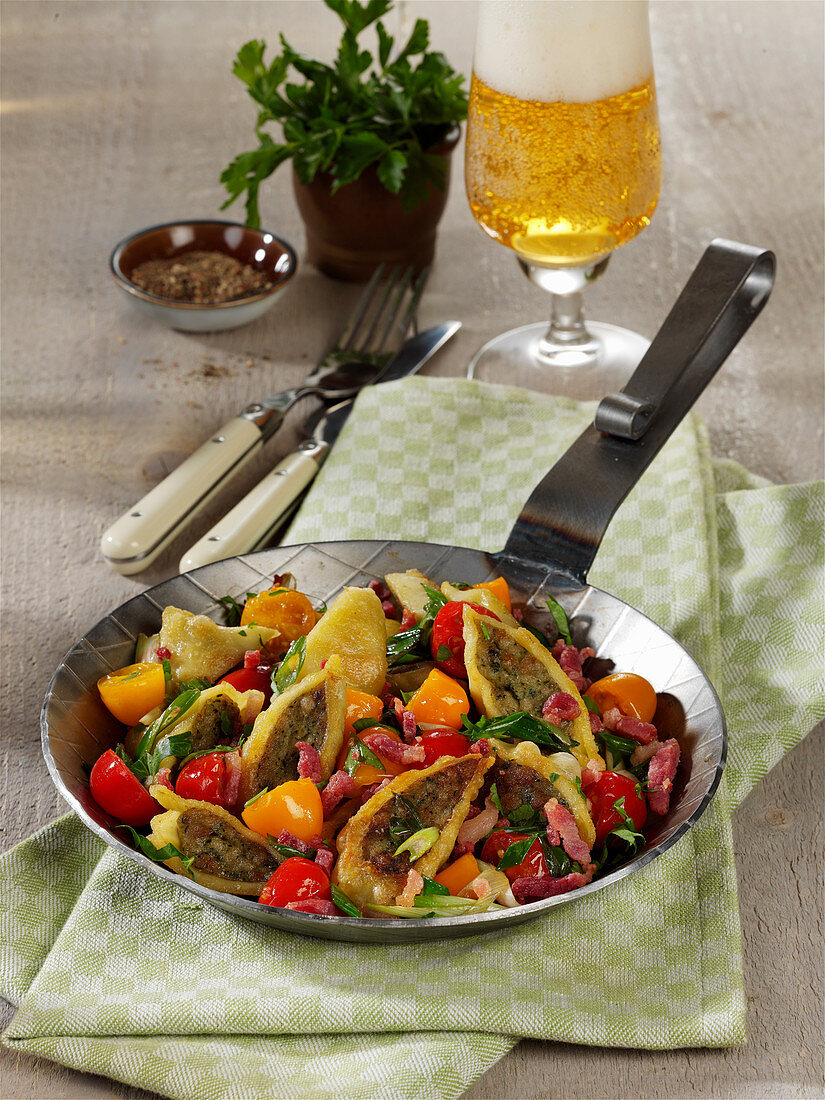 Fried Maultaschen (Swabian ravioli) with bacon, tomatoes and spring onions