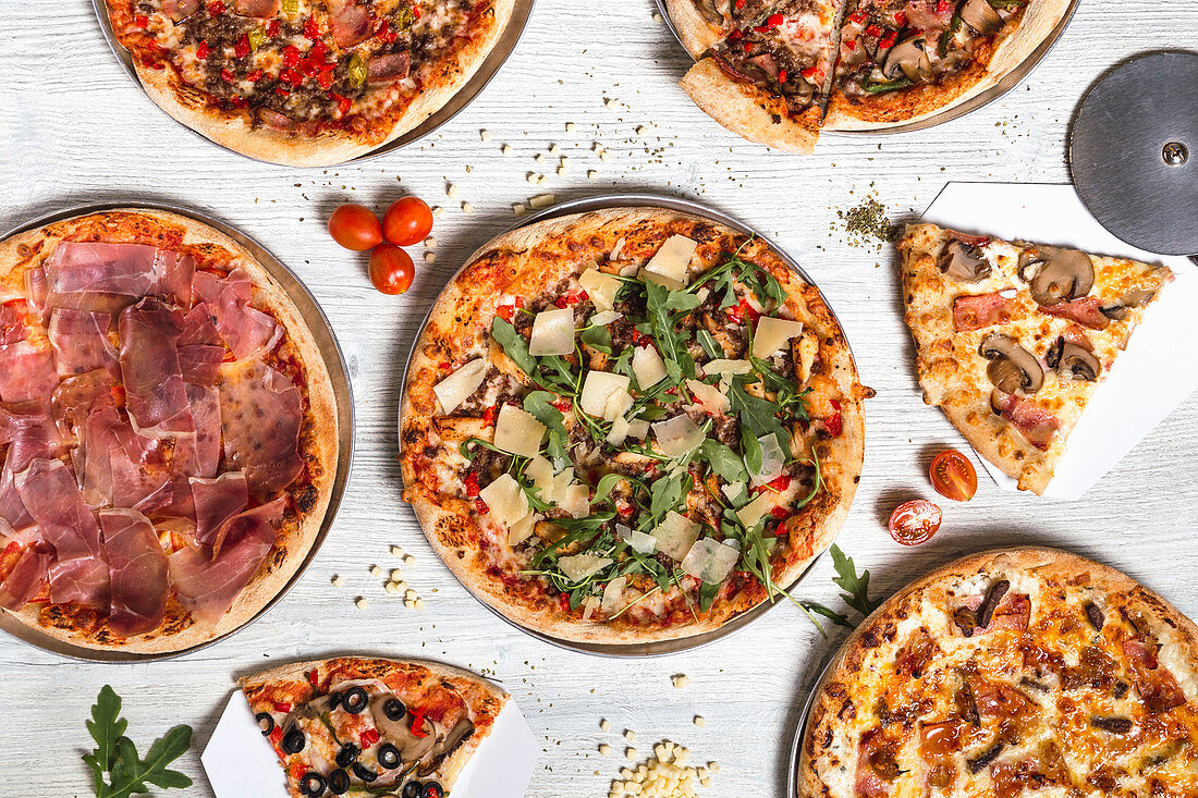 Pizzas with various meat and vegetables on white wooden table