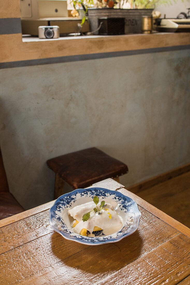 Ravioli garnished with bechamel sauce and sprig of fresh herb