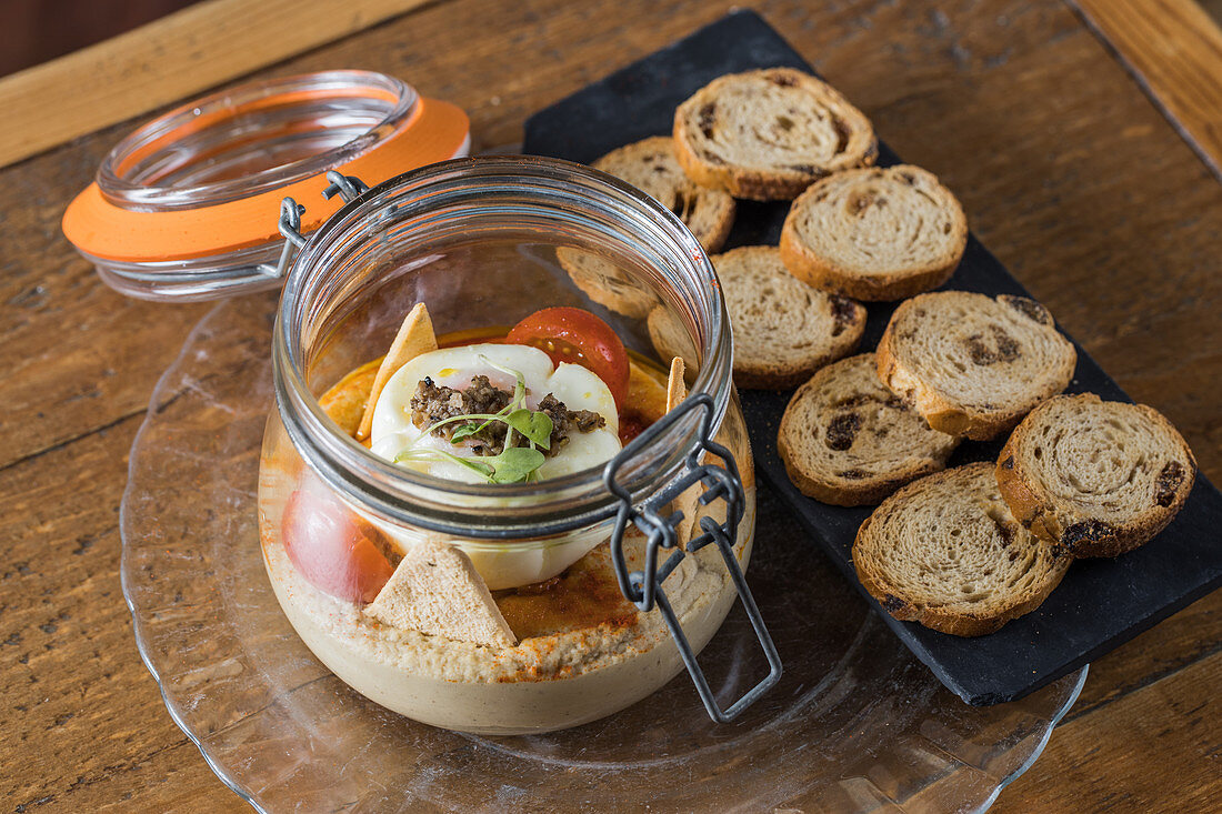 Chickpea hummus with truffle arranged with raisin bread on wooden table in restaurant