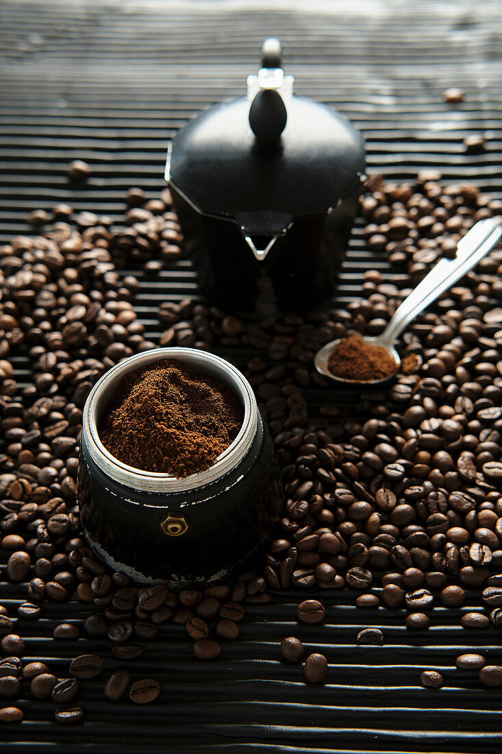 Ground coffee in traditional coffee maker placed on table with scattered roasted grains