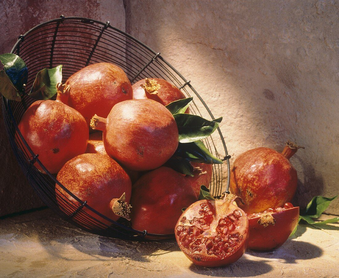 Whole Pomegranates in a Wire Basket; One Cut in Half