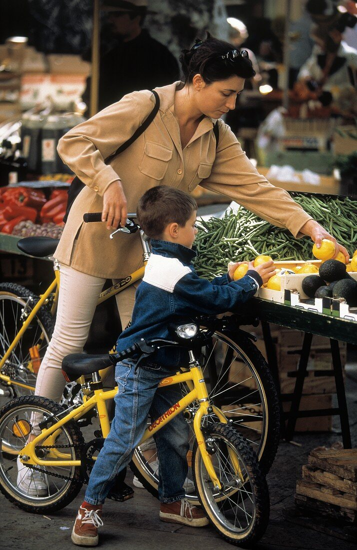 Woman and Young Boy on Bikes at a Vegetable Market