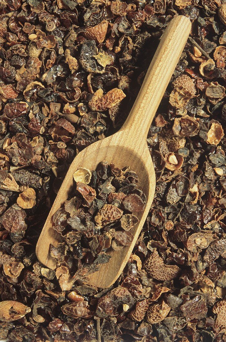 Dried rose hip skins (close-up with wooden scoop)