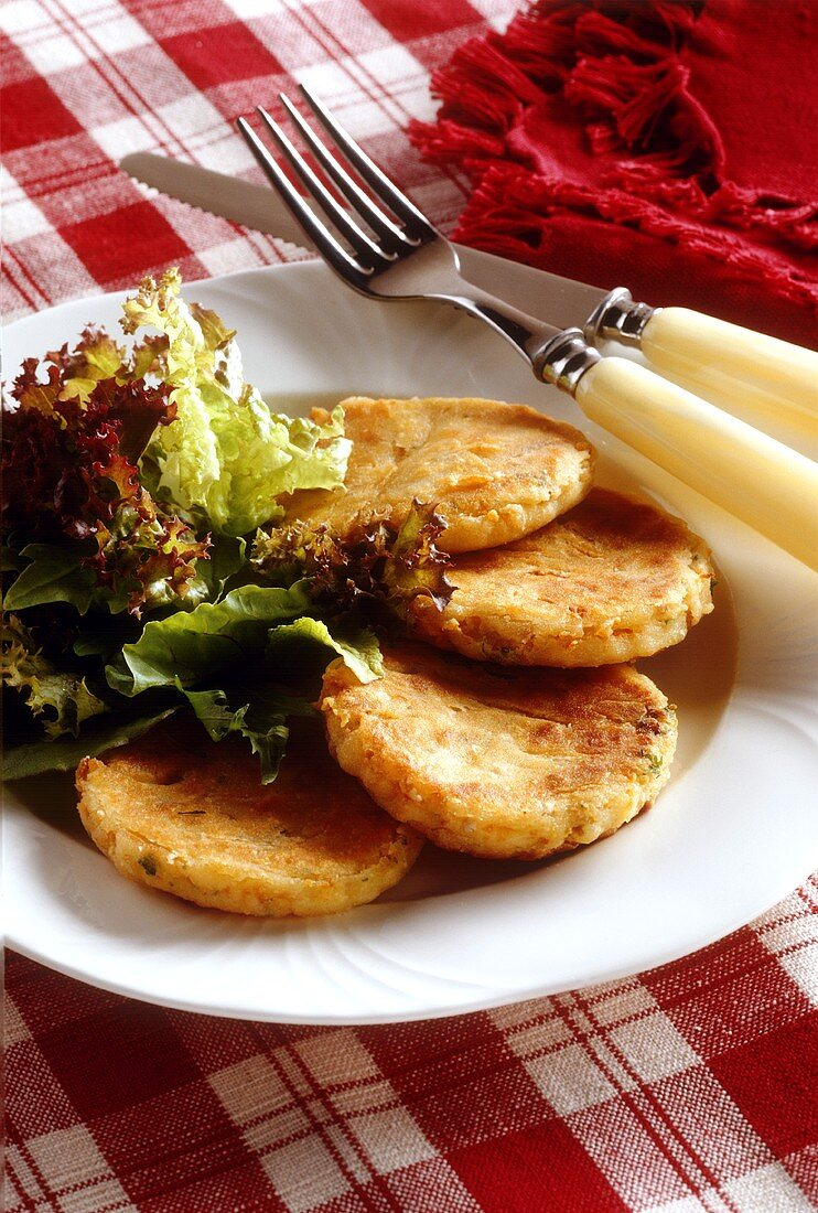 Carrot and celery burgers with green salad on plate