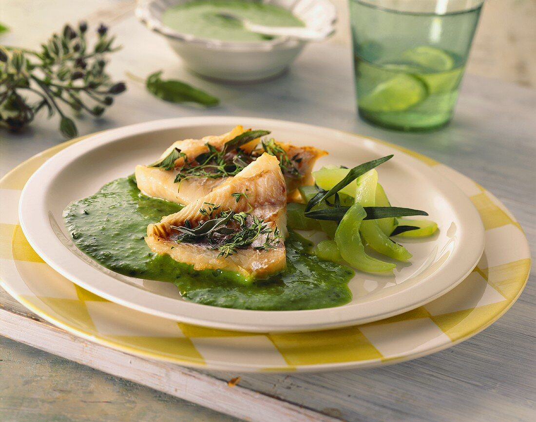 Red perch fillets with green sauce and cucumber on plate