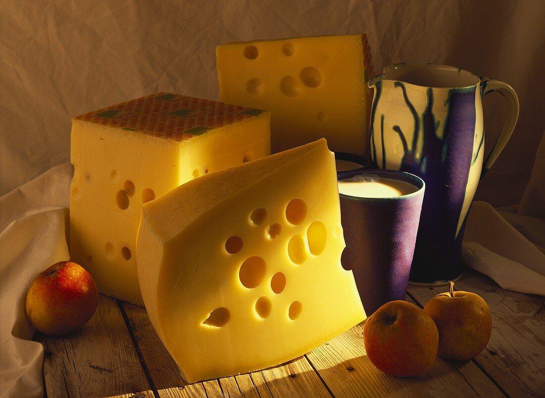 Pieces of Allgau Emmental cheese, milk beaker & jug, apples