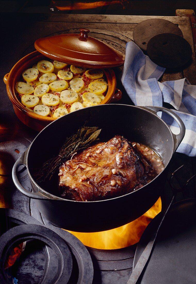 Roast wild boar in roasting dish on cooker, potato casserole
