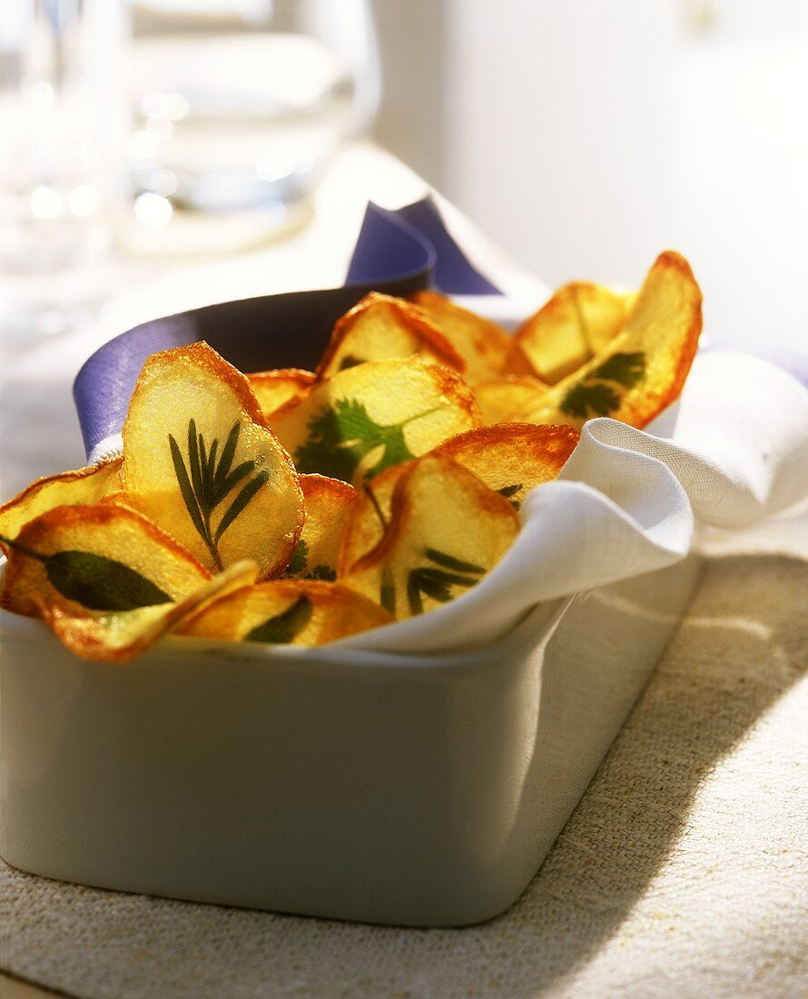Potato & herb crisps on kitchen cloth in square dish