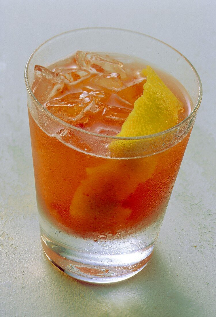 Strawberry drink with ice cream and lemon peel in glass