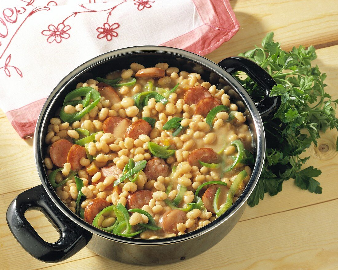 White bean stew with smoked sausage and leek in pot