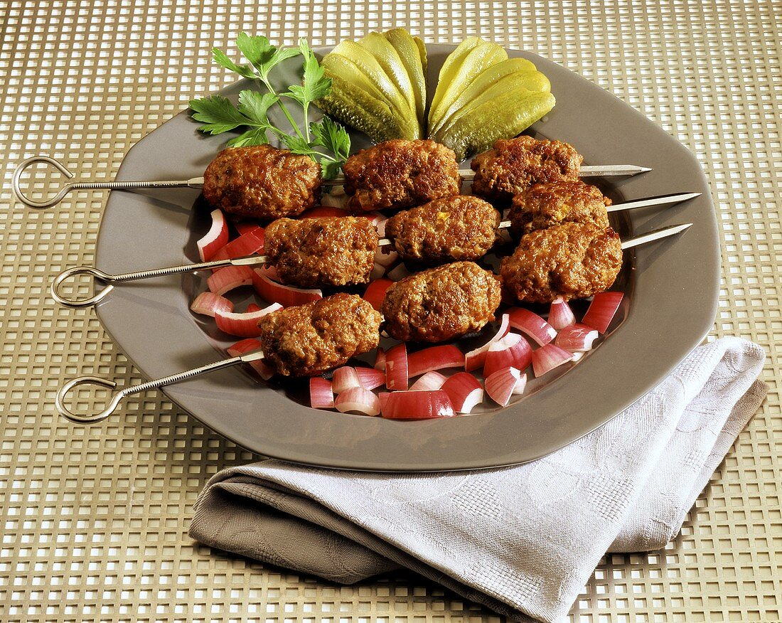 Cevapcici kebab on plate with onions and cucumber