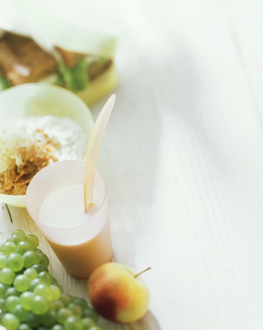 Still life with muesli, buttermilk in glass, apple & grapes