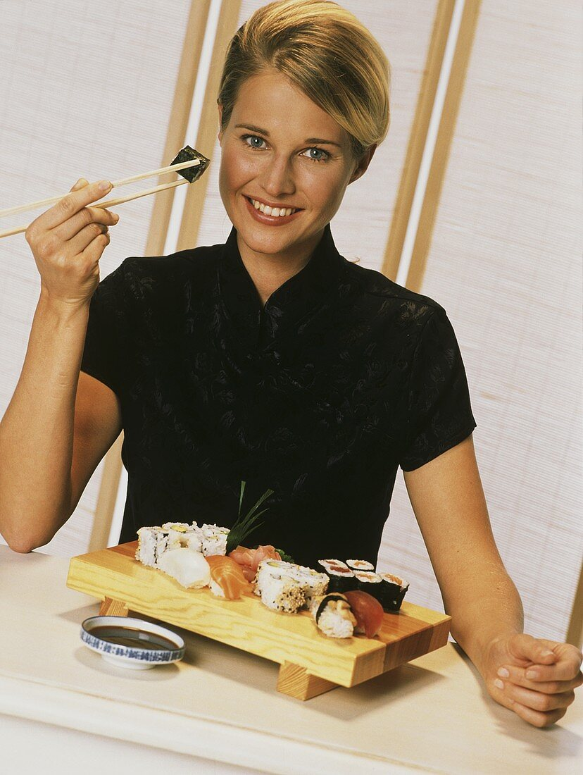 Young blond woman holding sushi with chopsticks